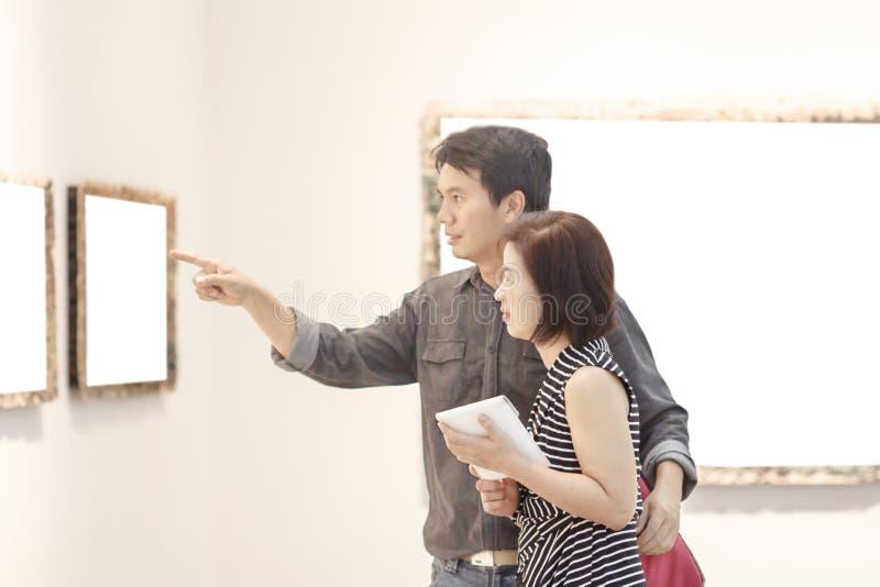 Asiático feliz dos pares que olha a galeria de arte foto de stock royalty free