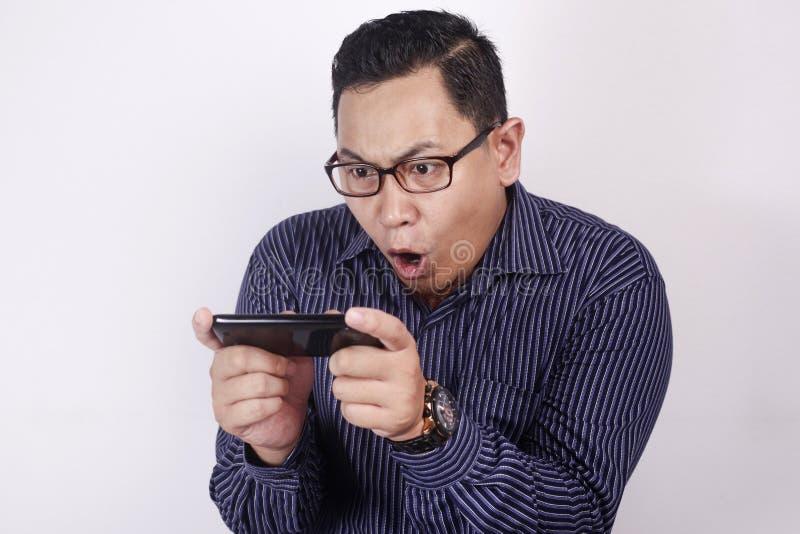 Asiático joven feliz Guy Playing Games en el teléfono elegante de la tableta fotografía de archivo