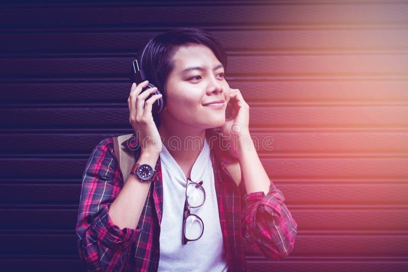 Asiático Las adolescencias están escuchando la música en la gama cercana con una puesta del sol ligera imagen de archivo libre de regalías