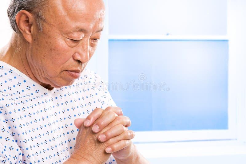 Asiático mayor de rogación en hospital foto de archivo