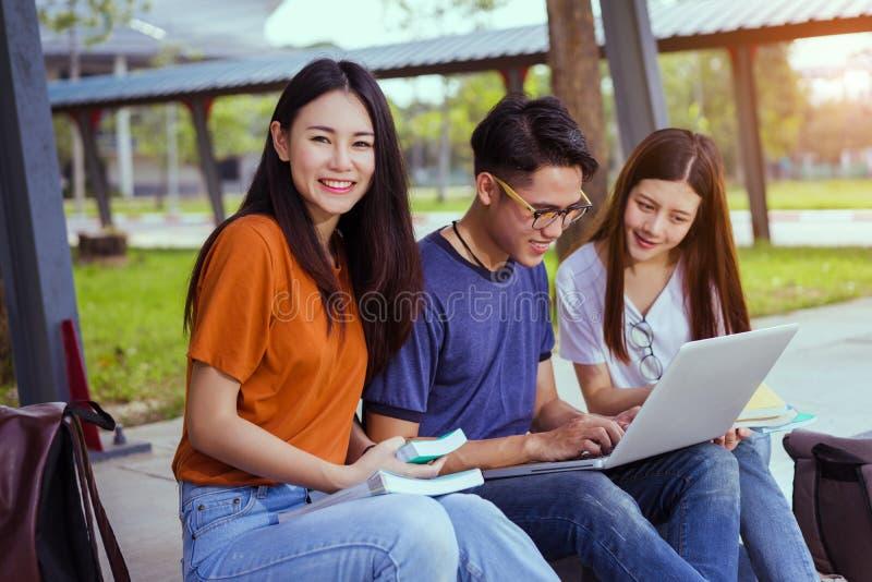 Asiático novo dos estudantes que lê junto o estudo do livro imagem de stock