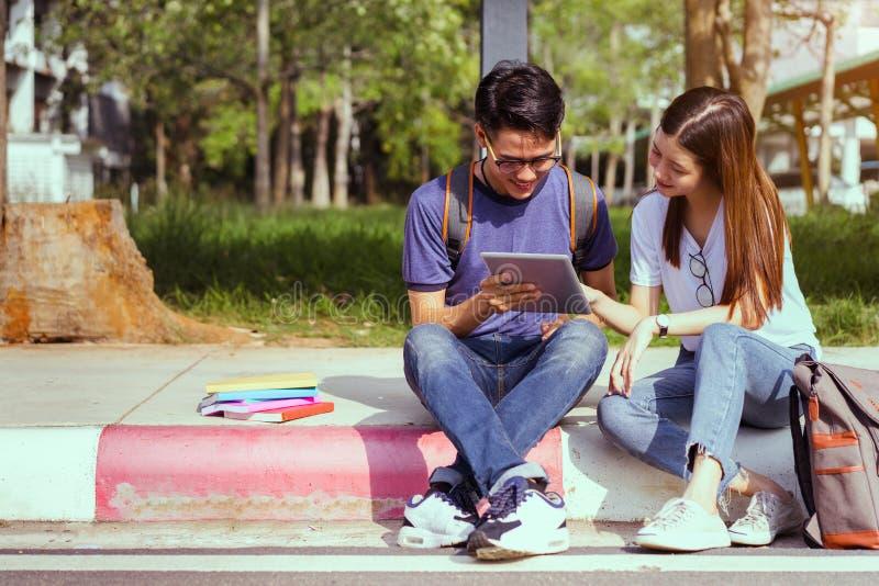 Asiático novo dos estudantes que usa junto o laptop imagens de stock