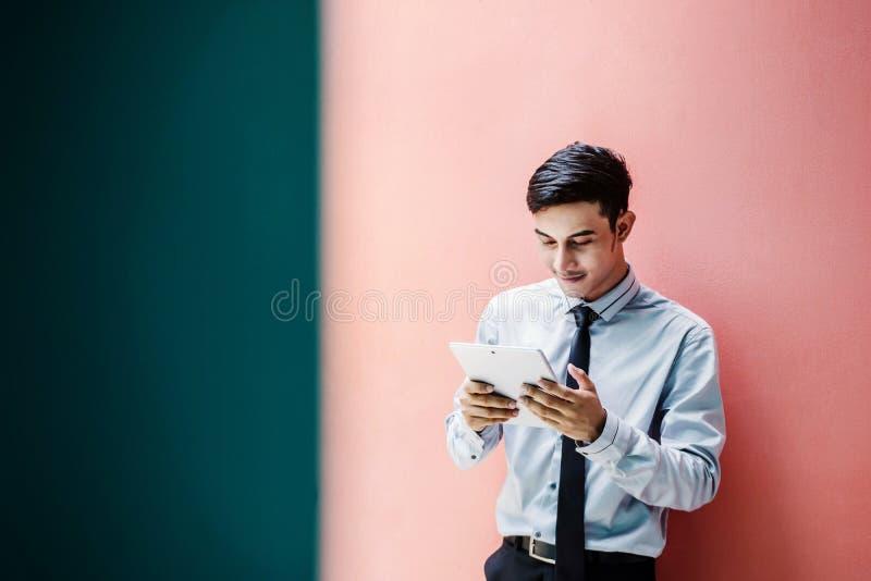 Asiático novo e homem de negócios feliz Reading ou trabalho em um digita fotografia de stock