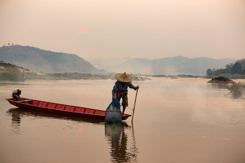 Asiático, peixe do cacth do pescador de Tailândia no boath de madeira no meko fotografia de stock