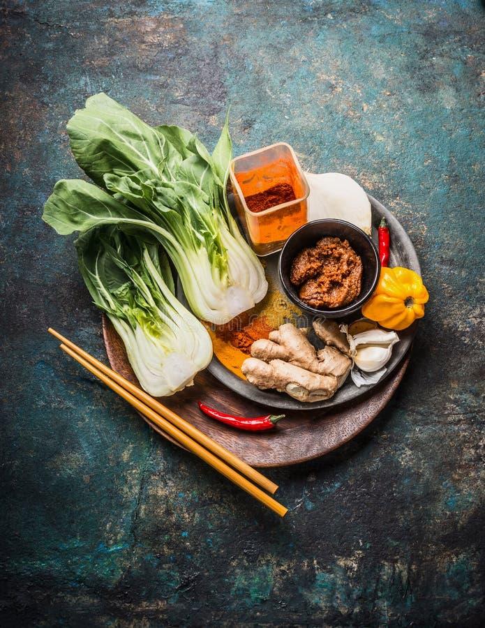 Asiático que cocina los ingredientes con pak choi, jengibre, especias, chile y palillos en el plato de madera para la cocina chin fotos de archivo libres de regalías