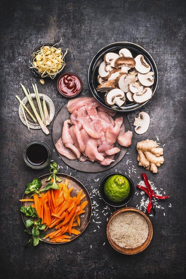 Asiático que cozinha ingredientes para o prato do arroz da galinha com os vegetais no fundo rústico escuro, vista superior fotos de stock royalty free