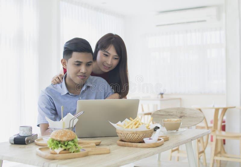 Asiático tailandês, par feliz do amor que trabalha com o portátil na casa fotos de stock