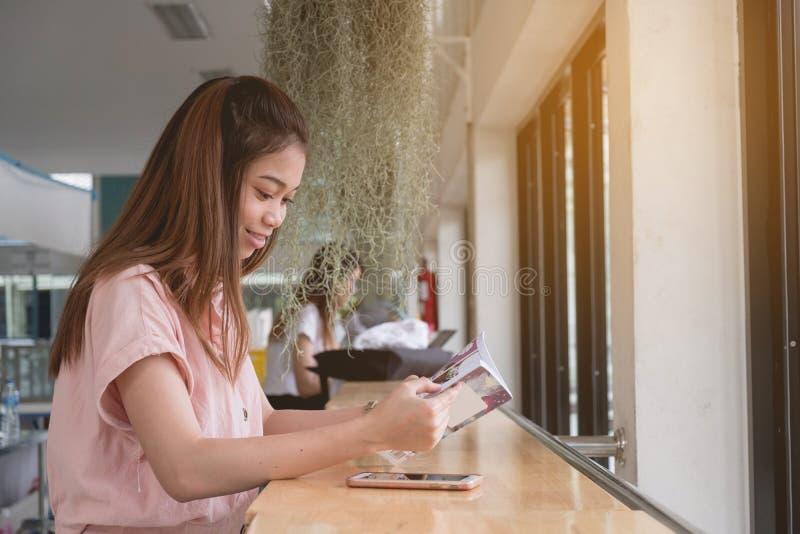 Asi?tico joven que lee el libro que se sienta en la barra del escritorio, concepto del estudio de la mujer foto de archivo libre de regalías