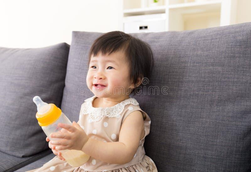 Asia baby holding milk bottle stock image