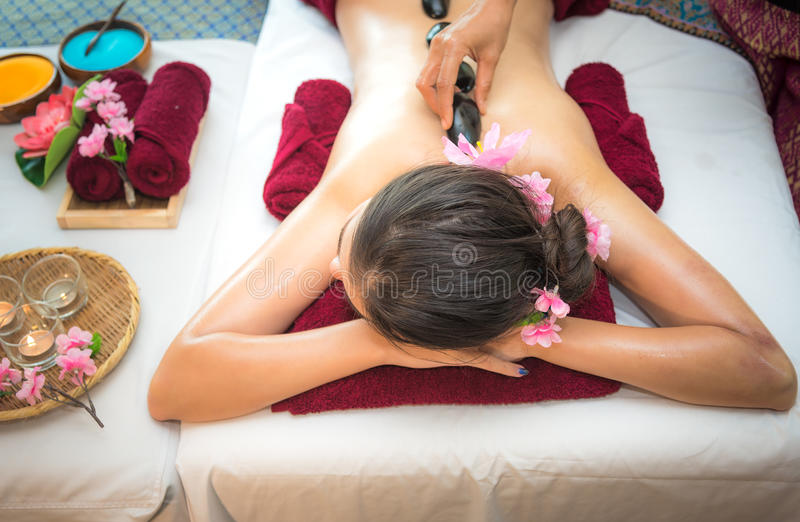 Asia beauty woman lying down on massage bed with traditional hot stones along the spine at Thai spa and wellness center, so relax. And lifestyle. Healthy royalty free stock image