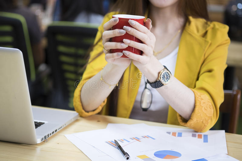 Asia businesswoman in office holding the red cup of coffee royalty free stock photo
