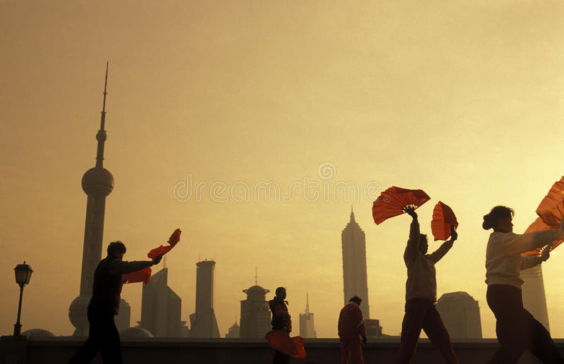 ASIA CHINA SHANGHAI PUDNONG. People celebrating tai chi in the morning on the Bund in front of the skyline of Pudong in the City Shanghai in China royalty free stock photo