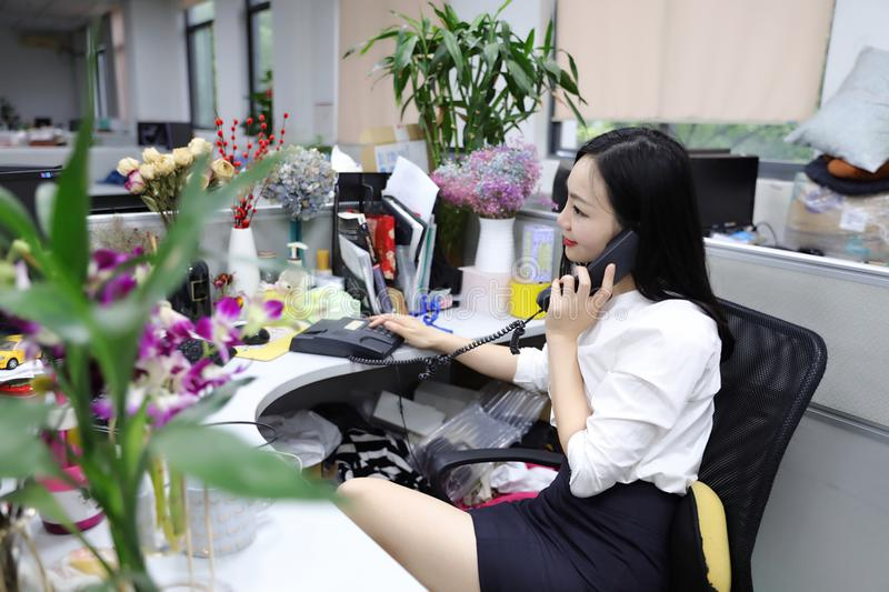 Asia Chinese office lady woman girl on chair make a call use desk phone chat work smile wear business occupation suit workplace royalty free stock image