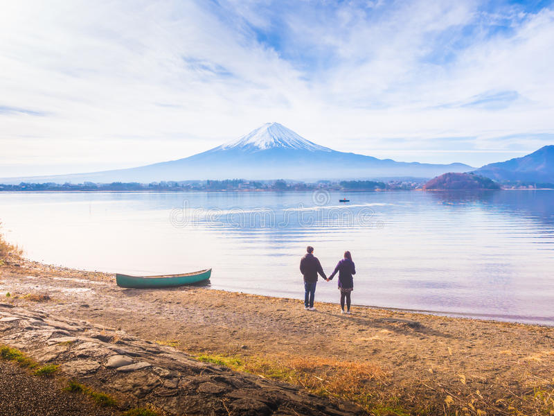 Asia couple traveler 30s to 40s stand by hold one& x27;s hands and ta. Ke picture with boat on ground at side of lake kawaguchi on morning time with fuji royalty free stock photos