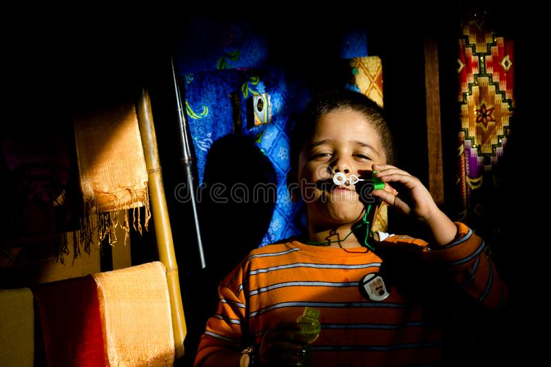 An asia ethnic child enjoys blowing soap bubbles. stock photography