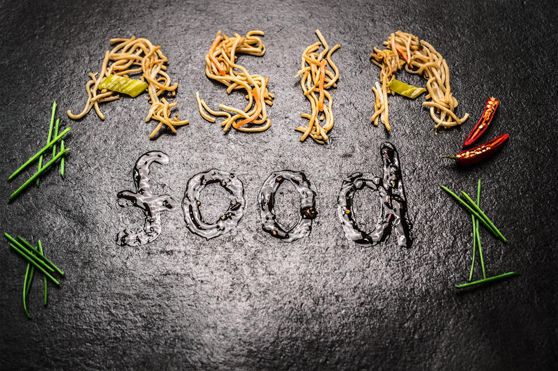 Asia food Inscription of noodles and sauce with red chili and chopped chives on black slate background stock photo