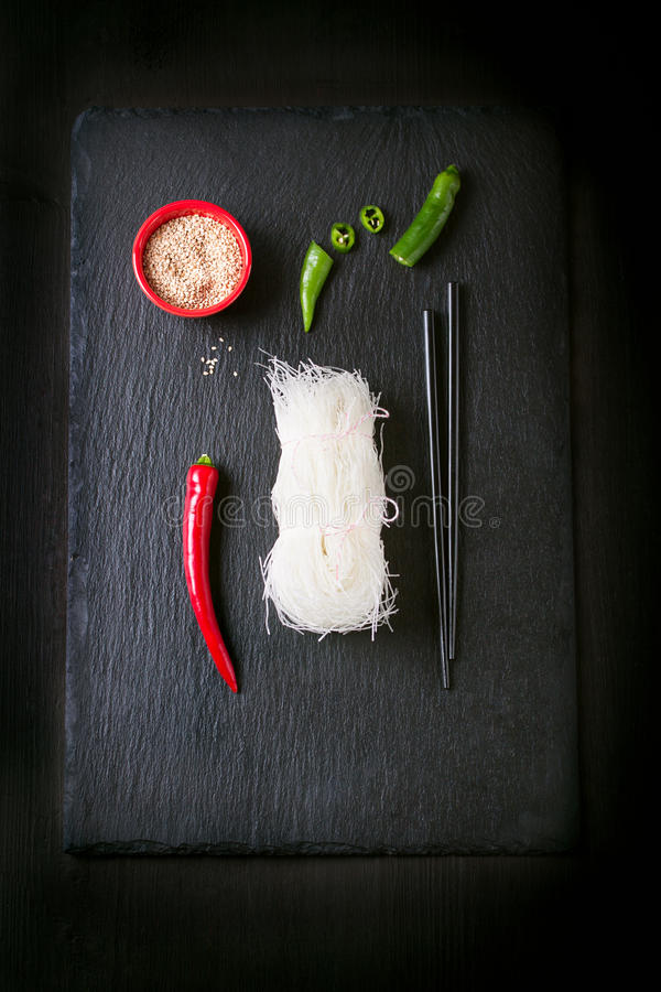 Asia food - rice noodles, spicy pepper, sticks and sesam, ready to cook on a dark stone background. Top view royalty free stock photo