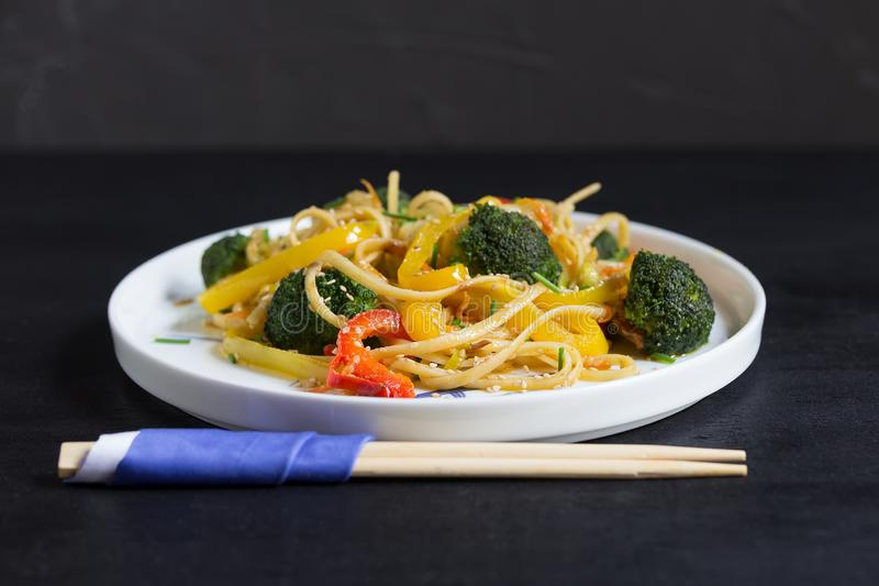 Asia food. Stir fry udon noodles with vegetables on the black backgound, cooked in wok stock image