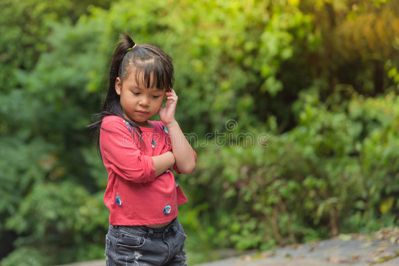 Asia Girl child in Red T-shirt confuse feelings. And thinking royalty free stock image