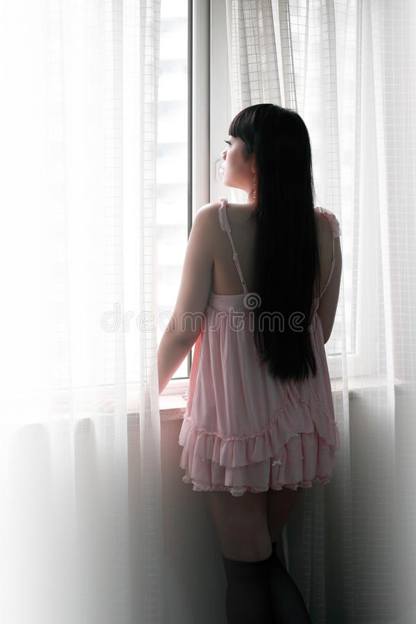 Asia girl standing by the window royalty free stock image