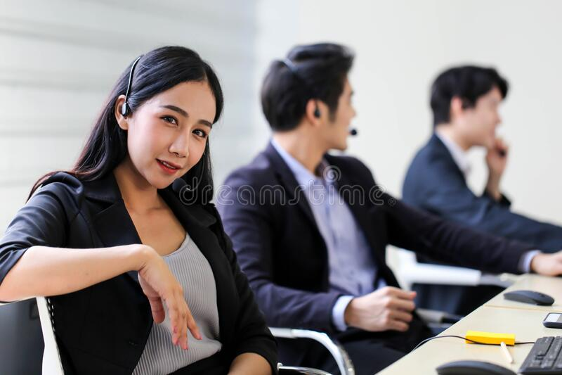 Asia Group of call center Workers o Confidential Business team con headset in office fotografia stock