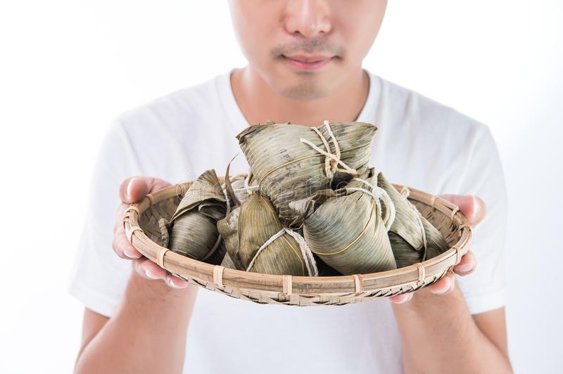 A Asia man is looking at Zongzi or rice dumpling with funny face and smile and is feeling interested in them on Dragon Boat Festiv royalty free stock image