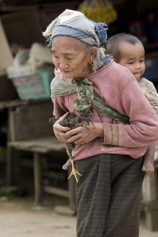 Asia, mujer mayor con el pollo y el nieto foto de archivo