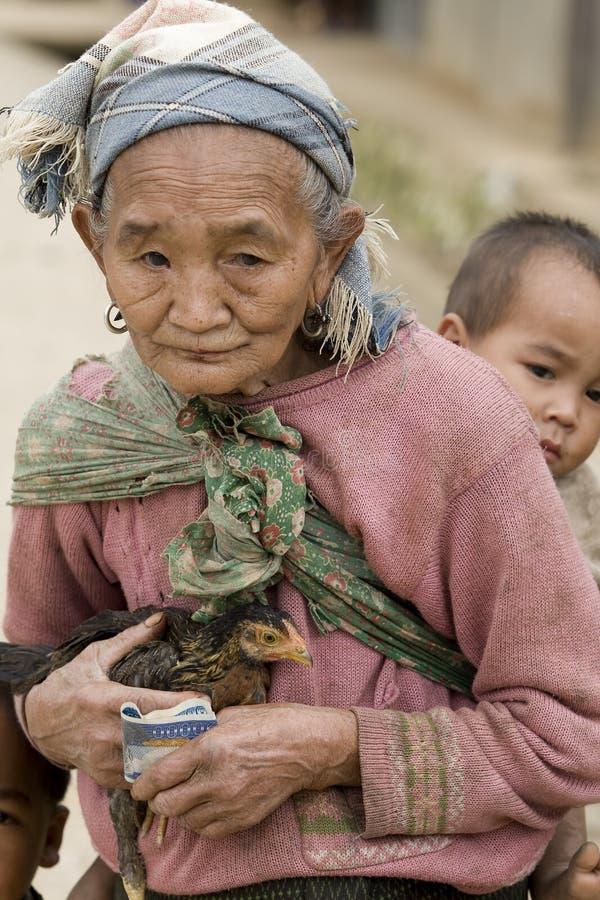 Asia, mujer mayor con el pollo y el nieto fotos de archivo