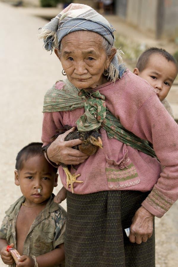 Asia, mujer mayor con el pollo y el nieto imagenes de archivo