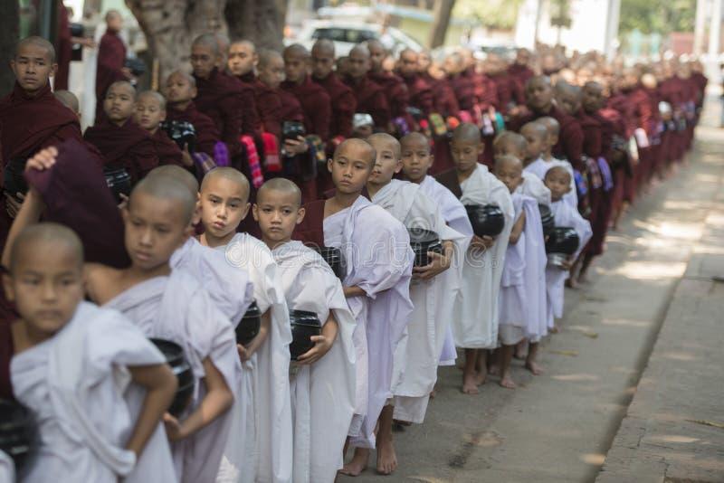 ASIA MYANMAR MANDALAY AMARAPURA MAHA GANAYON KYAUNG MONASTERY. Monks are on the way to the lunch at the Mahagandayon Monastery in Amarapura near the City of royalty free stock images