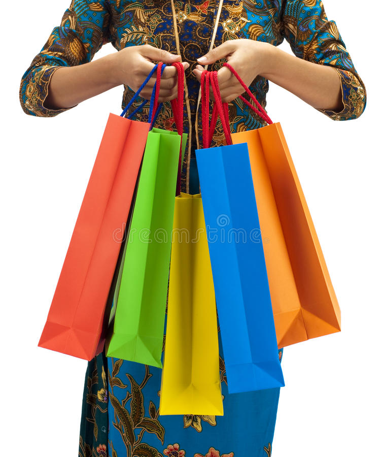 Asia shopping paradise. Woman in tradition Kebaya holding colorful shopping bag royalty free stock image