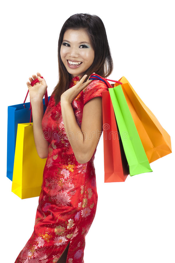 Asia shopping paradise. Woman in tradition Cheongsam holding colorful shopping bag stock photo