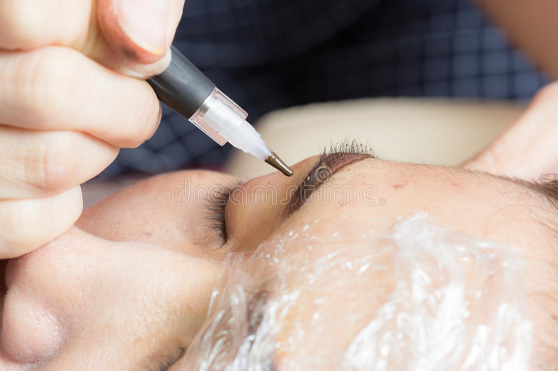 Asia woman applying permanent make up eyebrows tattoo. stock photo