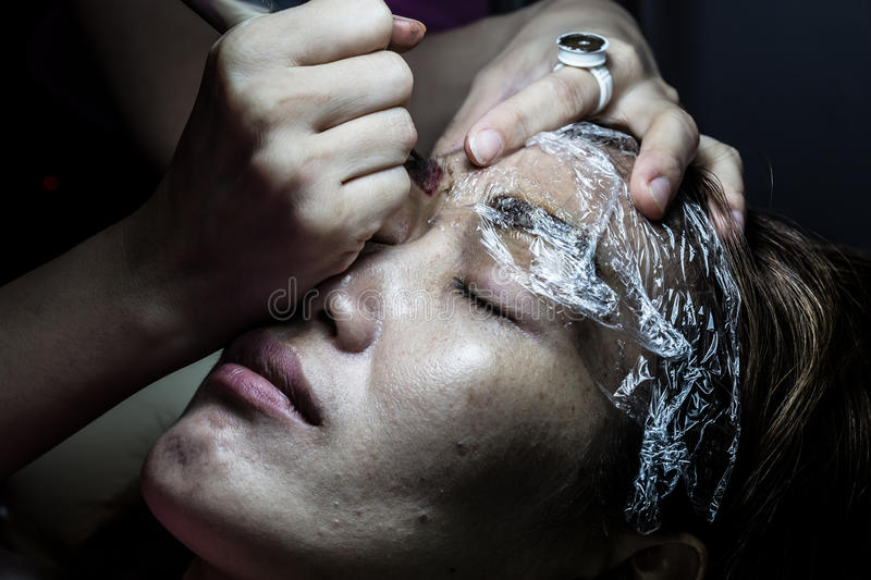 Asia woman applying permanent make up eyebrows tattoo. royalty free stock photography