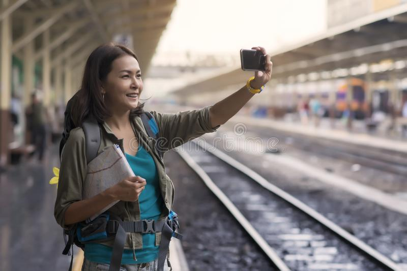 Asia woman with backpack and map, she taking photo with smartphone at railway while stand waitting train. Asia woman with backpack and map, she taking photo stock photos