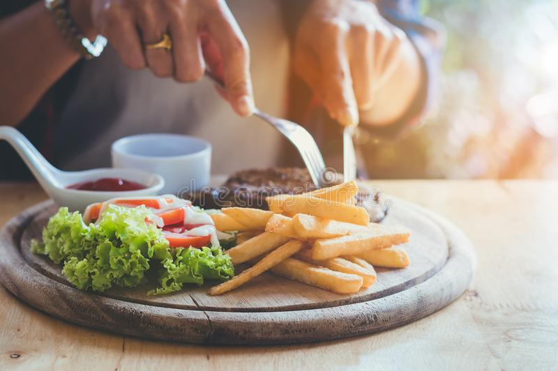 Asia woman`s hands eating meat steak with fun and happy. Asia woman eating meat steak and salad on wooden round plate at restaurant ,home with fun and happy royalty free stock image