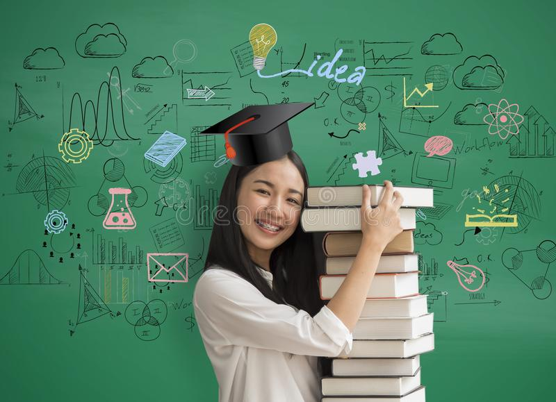 Asia women student holding book with with graduation hat on math stock photo