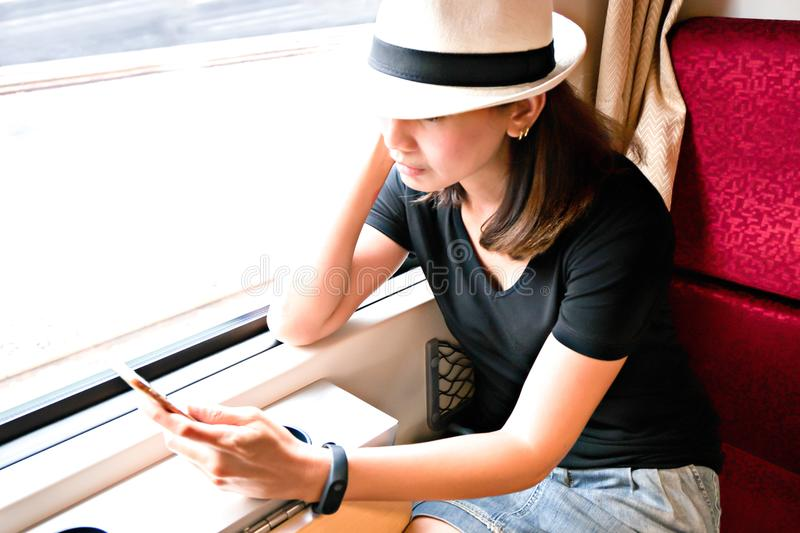 Asia woman using smart phone in the train. Travel with technology concept stock images