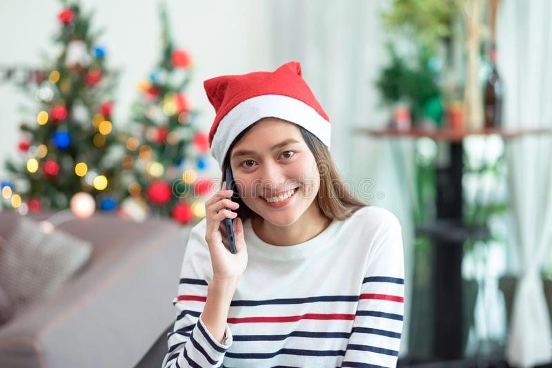 Asia woman wear santa hat and holding gift box and use mobile ta. Lk with friend and sitting on sofa in christmas party,holiday celebration concept royalty free stock images
