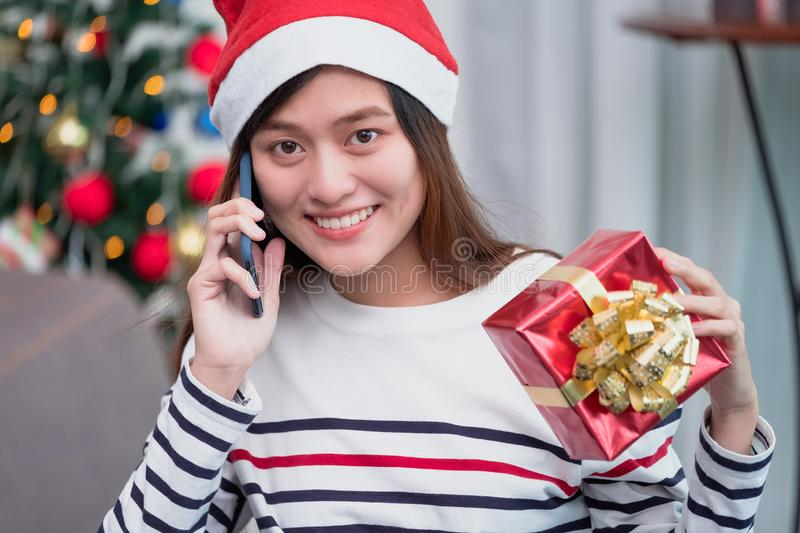 Asia woman wear santa hat and holding gift box and use mobile ta. Lk with friend and sitting on sofa in christmas party,holiday celebration concept stock photos