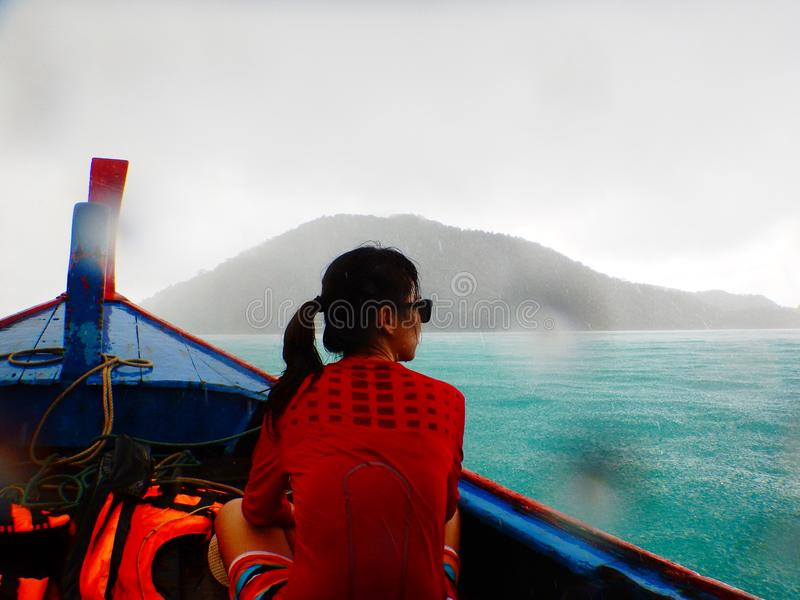 Asia woman wearing red shirt sitting on longtail boat while rain. Young asia woman wearing red shirt sitting on longtail boat while rainy makes herself wet moist stock images