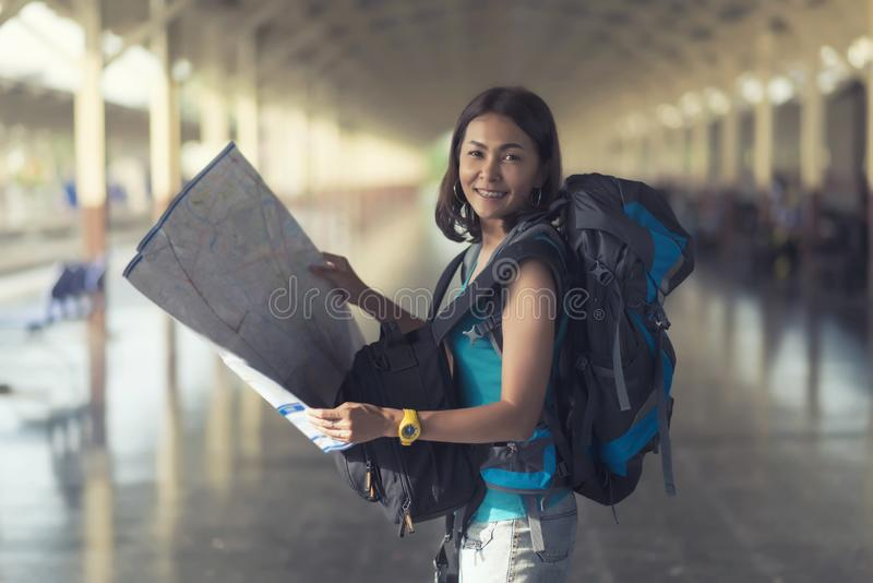 Asia women with bag backpack and holding map, preparing for traveler trip at train station. Asia woman with bag backpack and holding map, preparing for traveler royalty free stock images