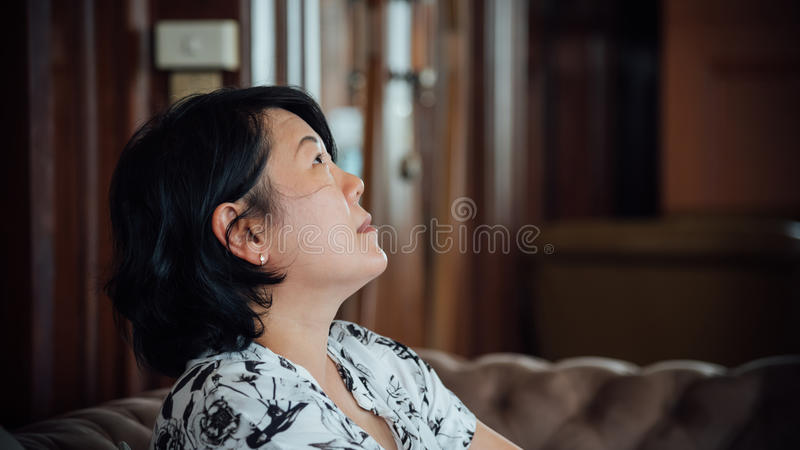 Asia women look up in coffee shop vintage style. Asia woman 40s white skin in white and black dress have a lovely look up gesture wait for something in a coffee stock image