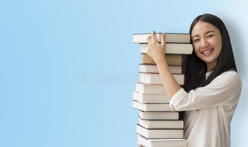 Asia women student holding book on blue background in school stock photos