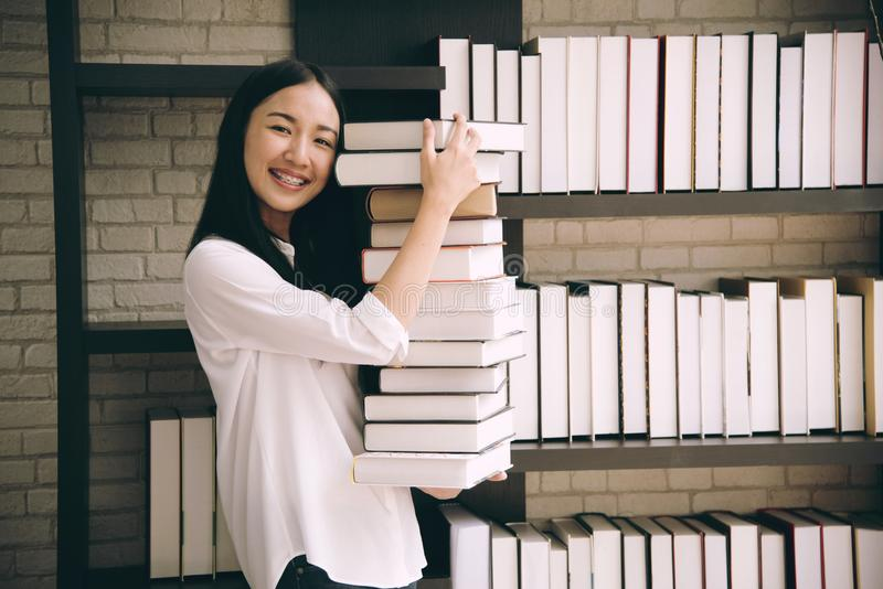 Asia women student holding book in library school royalty free stock image