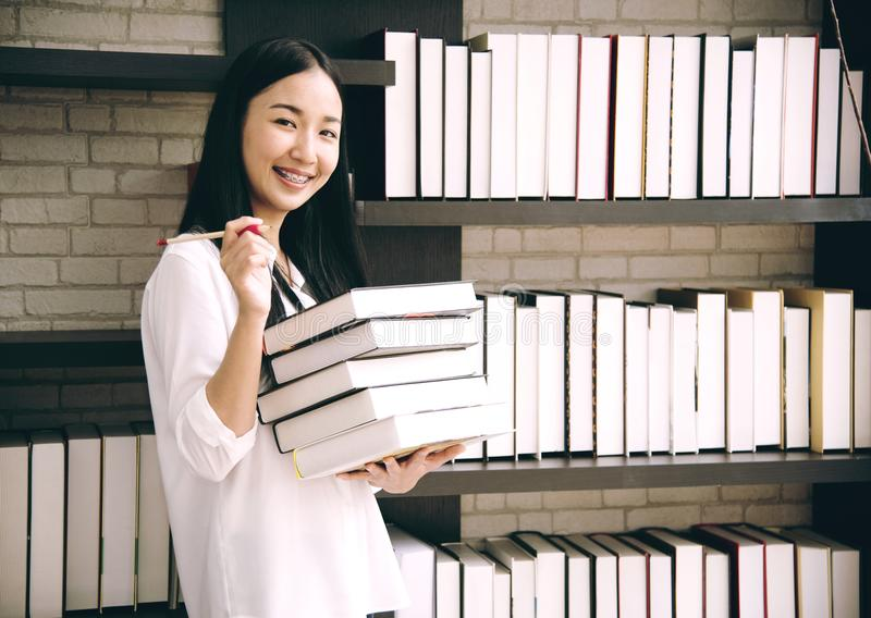 Asia women student holding book in library school stock photos