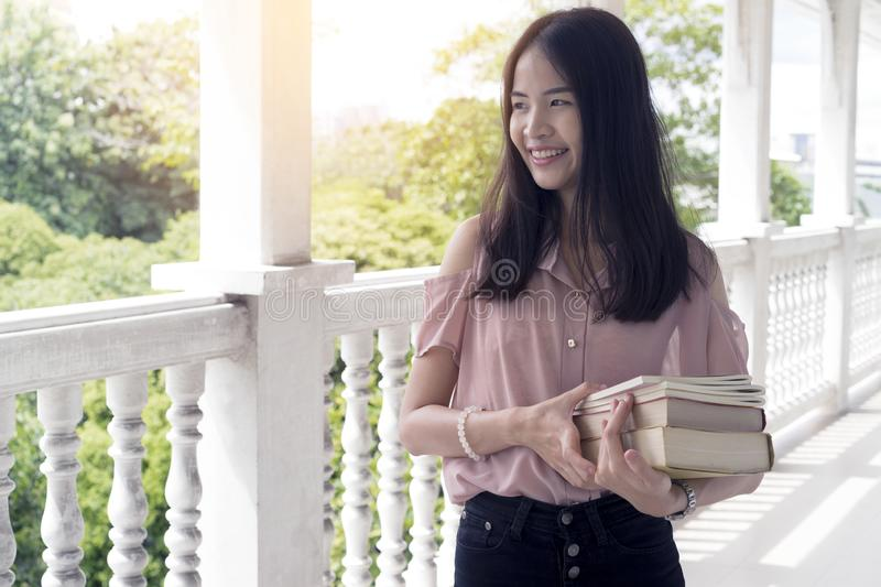 Asia young college student holding a books in front of classroom. Learning and Education concept royalty free stock photos