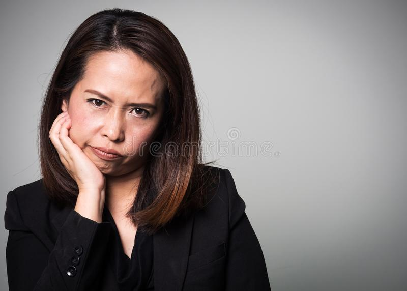 Asian adult woman boring face. Portrait of business women in black suit on white background. stock photos