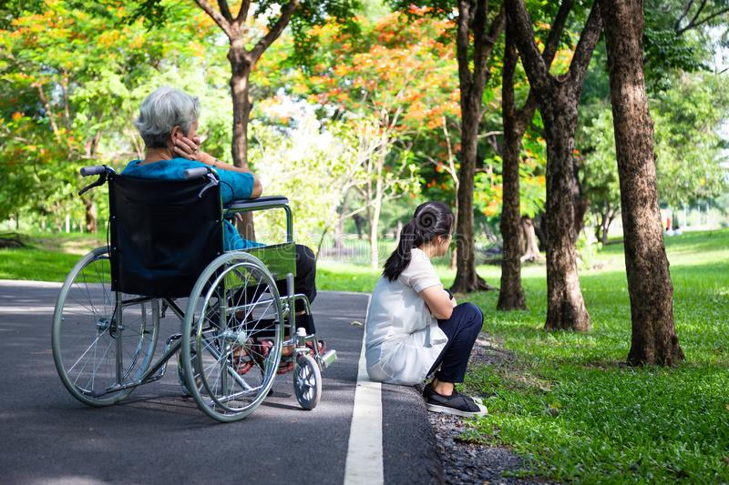 Asian adult woman touchy and angry acting with elderly people in wheelchair after senior mother argument,argue with daughter in. Asian adult women touchy and royalty free stock photography