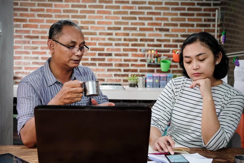 Asian Adults and Mature Business Partners Working Together at Home Office. Asian ethnic male and female business partners are working together in front of a royalty free stock image
